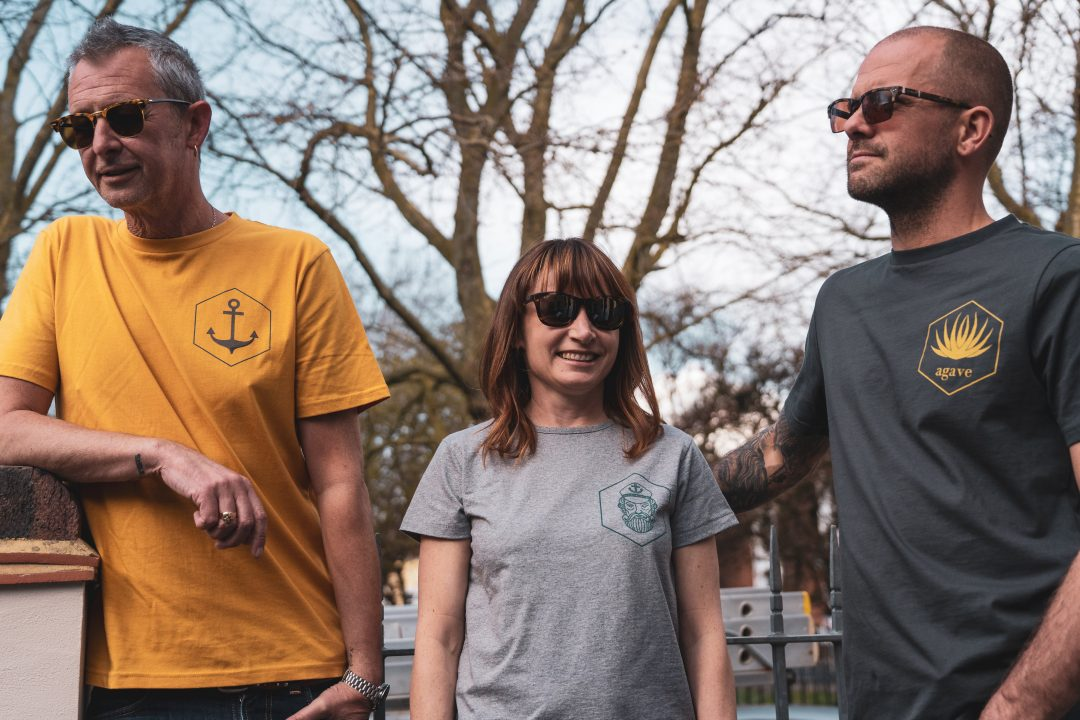 A woman and two men standing outside modelling different t-shirts from sustainable clothing brand Tabby Firefly