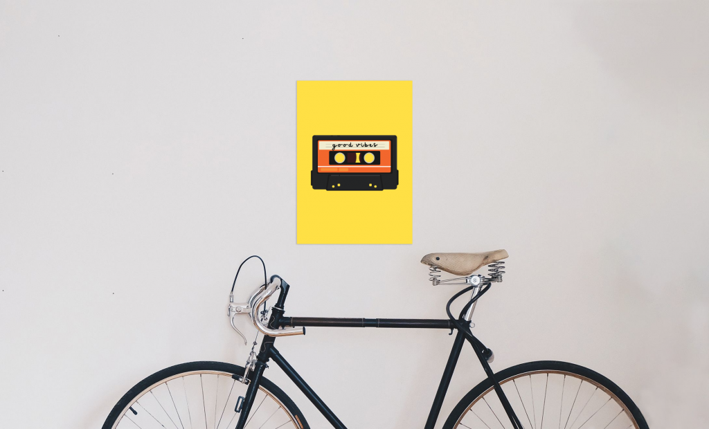 A picture of a wall with a bike leaning against it. On the wall above the bike there is a yellow poster with a cassette on saying 'good vibes'