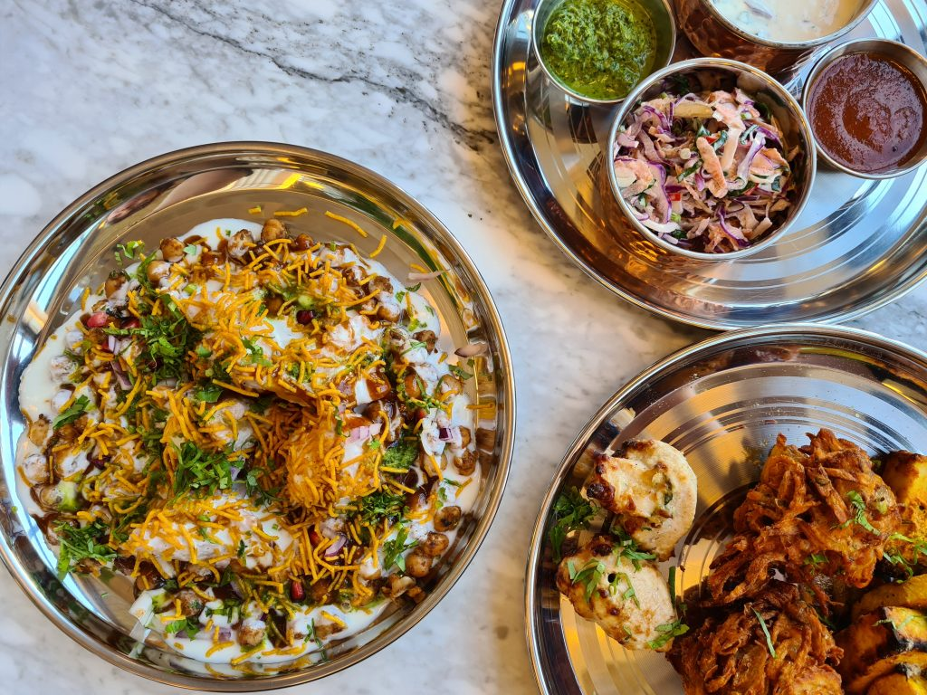 Looking down at three silver plates with different dishes of Indian food at Desi Old India Cafe, Southsea