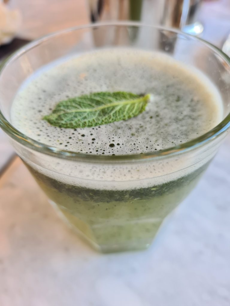 Green-coloured Lemon & Mint Shorbot drink in a glass with a mint leaf on the top, at Desi Old India Cafe, Southsea
