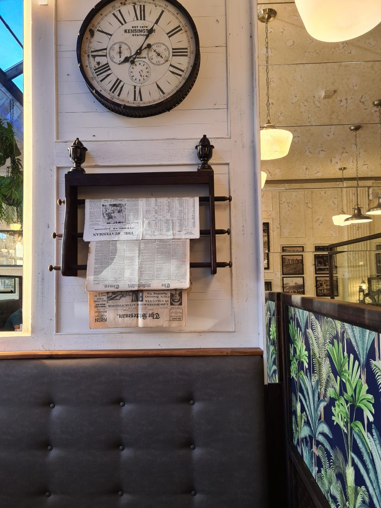 A photo of seating at Desi Old India Cafe showing a bench seat, a clock and a newspaper rack